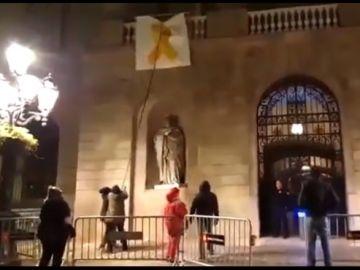 Un grupo de personas retiran el lazo amarillo del Ayuntamiento de Barcelona