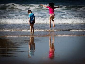 Dos niños disfrutan de otro día soleado en la orilla de la playa
