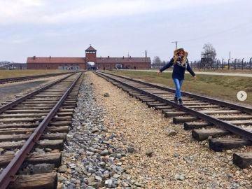 Una joven haciendo equilibro en las vías del tren
