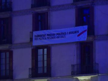 La pancarta retira de la Generalitat aparece colgada en un edificio particular en Sant Jaume