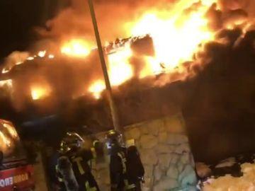 Un total de ocho dotaciones de bomberos trabajan para extinguir un incendio en un chalet de madera en Madrid