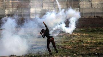 Un palestino devuelve una granada de gas lacrimógeno durante protestas en la frontera entre Israel y Palestina