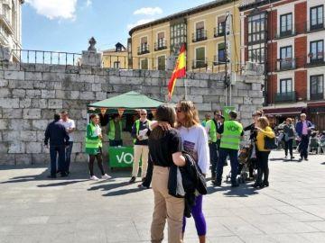 La pareja besándose frente al puesto de Vox