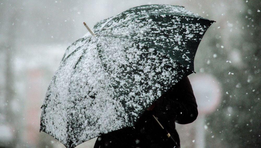 Una mujer protegiéndose de la nieve con un paraguas
