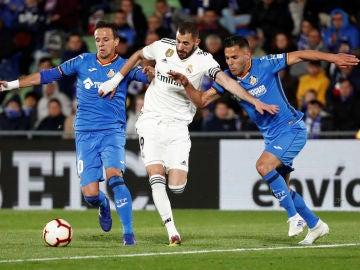 Benzema conduce el balón ante la defensa de los jugadores del Getafe