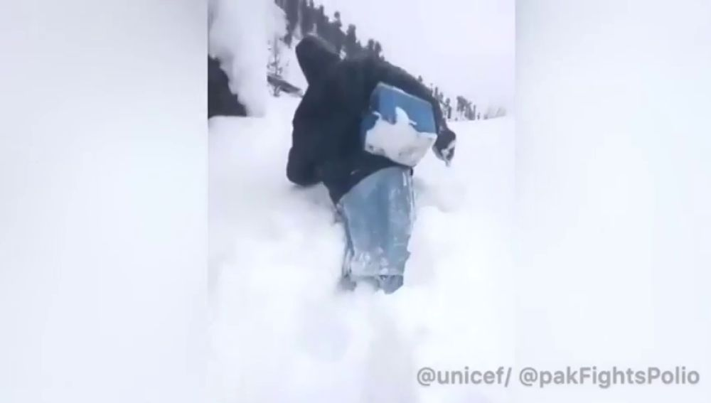 Un hombre se abre paso por la nieve para llevar vacunas a niños en Pakistán