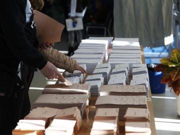 Imagen de una mesa con las papeletas electorales en uno de los colegios