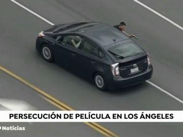 Un helicóptero graba como un hombre saca medio cuerpo por la ventanilla de su coche para disparar a la policía mientras huía