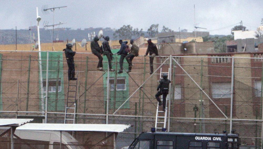 Imagen de archivo de migrantes subidos a la valla de Melilla