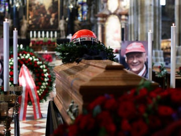 Un retrato del piloto austriaco Niki Lauda colocado junto a su ataúd y su casco en la capilla ardiente
