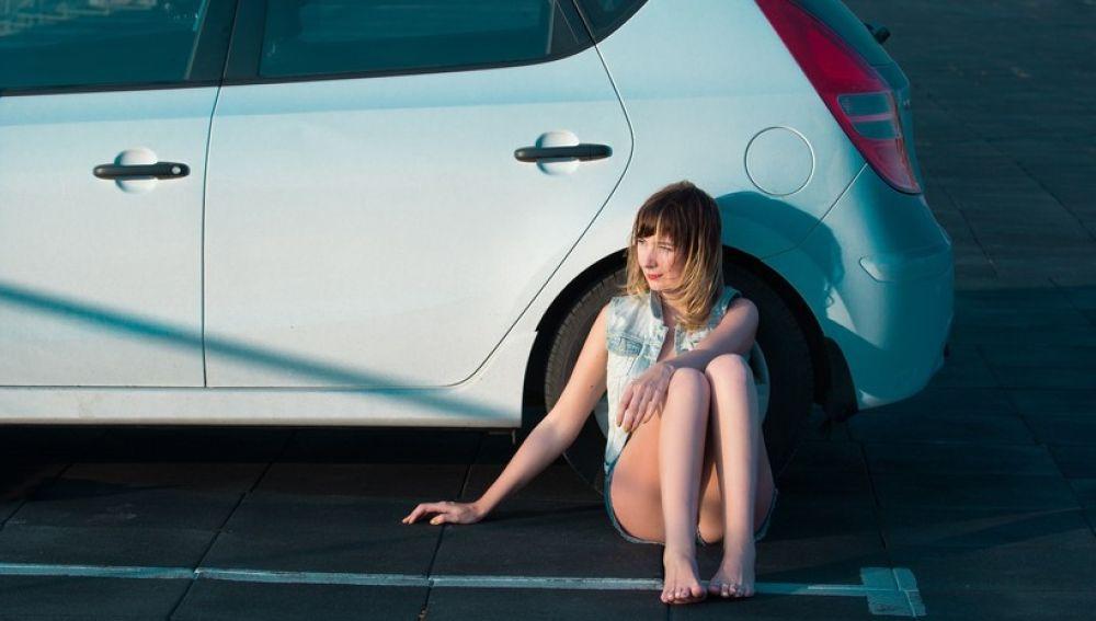 Mujer junto a un coche