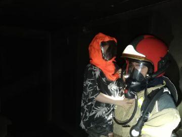 Un bombero de Valladolid con uno de los niños evacuados del incendio