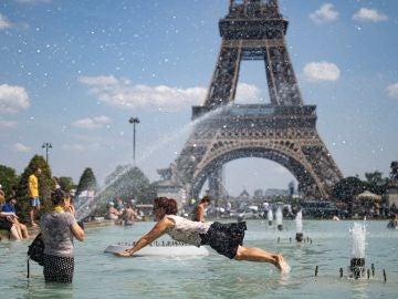 Personas refrescándose en la fuente de la Plaza del Trocadero, frente a la Torre Eiffel en París