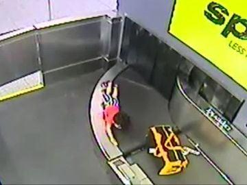 Un niño en una cinta transportadora de maletas