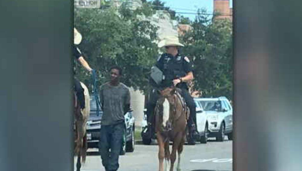 Dos policías llevan maniatado a un hombre negro detenido