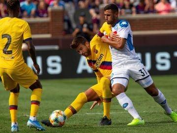 Gerard Piqué pelea un balón con un jugador del Nápoles