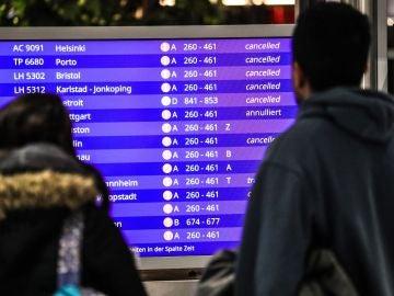 Unos pasajeros mirando los vuelos cancelados en la pantalla informativa