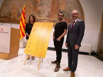 La consellera de Presidencia, Meritxell Budó, y el vicepresidente del Parlament, Josep Costa, acompañados del creador artístico del cartel del acto oficial de la Diada.