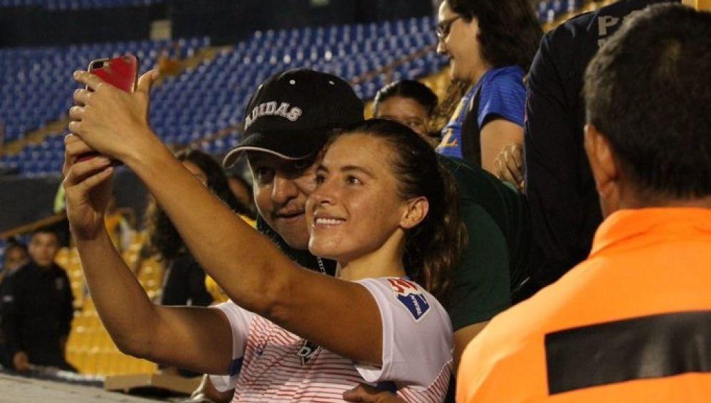 Un aficionado toca un pecho a una jugadora mientras se sacan una foto