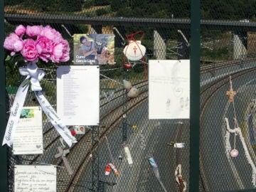 Diversos objetos en recuerdo y homenaje de las víctimas cuelgan de la valla en el paso elevado sobre la curva de A Grandeira
