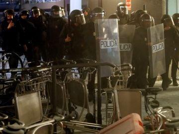 Policías antidisturbios durante los altercados que se han producido en el parking del aeropuerto El Prat