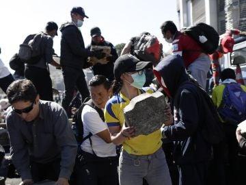 Un grupo de personas usa mascarillas sanitarias en las labores de limpieza