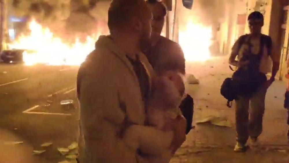 Un hombre sale con su bebé en brazos huyendo de las llamas que amenazan su casa por las protestas en Barcelona