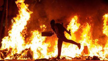 Un manifestante echa al fuego un cartón junto a la Delegación del Gobierno en Barcelona
