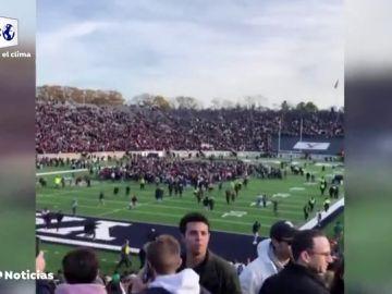 Manifestantes invaden el campo durante el descanso de un partido de fútbol americano para protestar contra el cambio climático