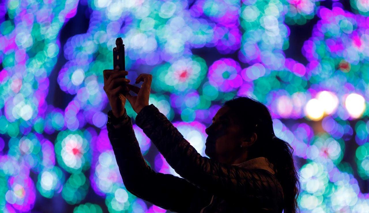 Una joven fotografía el árbol de Navidad de la Puerta del Sol.