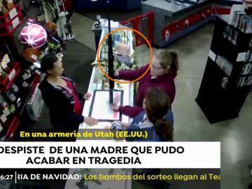 Un bebé, a punto de caer de un mostrador mientras su madre escogía un arma