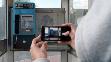 Una joven toma con su teléfono móvil una fotografía de una cabina telefónica en un barrio de Ávila