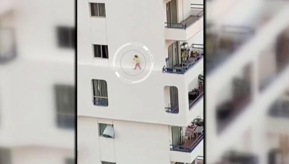 Una niña corretea peligrosamente por la cornisa de un edificio de apartamentos en Adeje