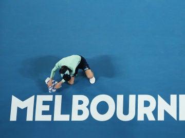 Una recogepelotas prepara una pista en el Open de Australia