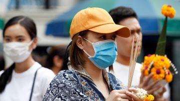 Una mujer se protege con una mascarilla