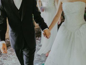 Unos novios cogidos de la mano en su boda