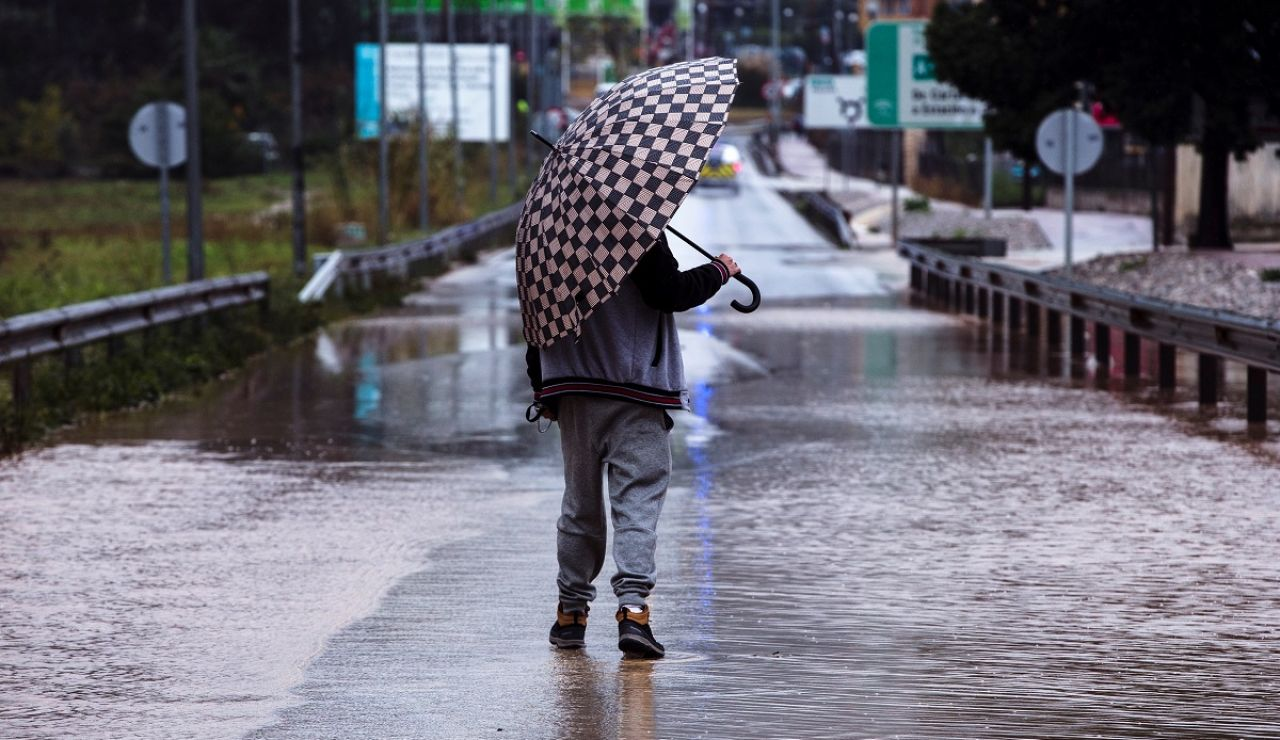 Un hombre se resguarda de la lluvia con un paraguas