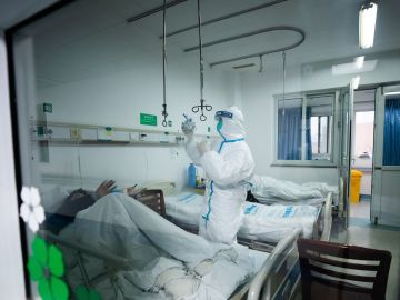 Un sanitario atendiendo a un paciente en un hospital de Wuhan, China