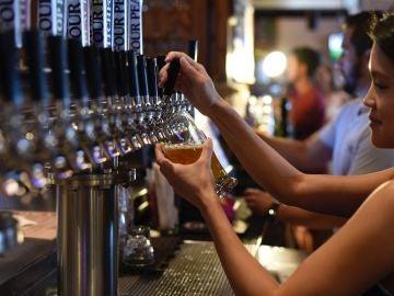 Una camarera sirviendo cerveza en un bar