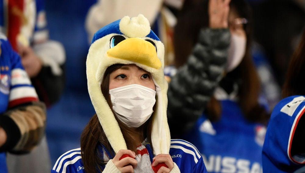 Una aficionada japonesa se protege de un posible contagio de coronavirus con una mascarilla