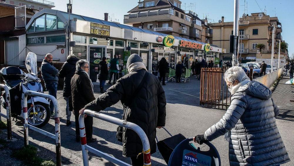 Personas en fila para entrar al supermercado en Italia