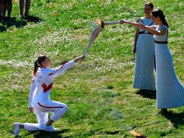 La primera relevista de la antorcha olímpica recibe el fuego olímpico