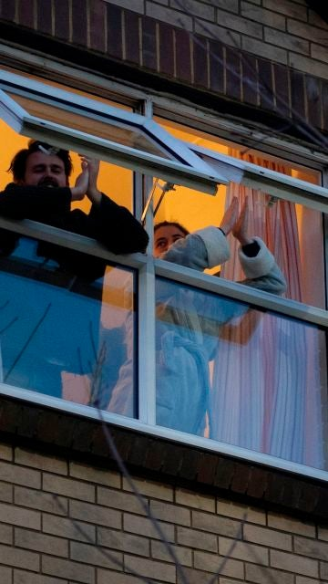 Dos personas asonadas a una ventana