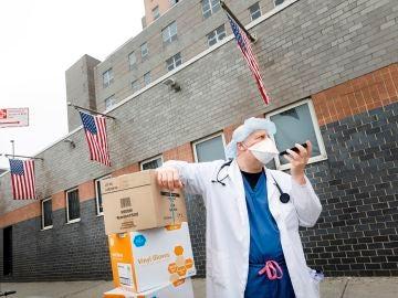 Un sanitario habla por teléfono en Nueva York con la mascarilla puesta