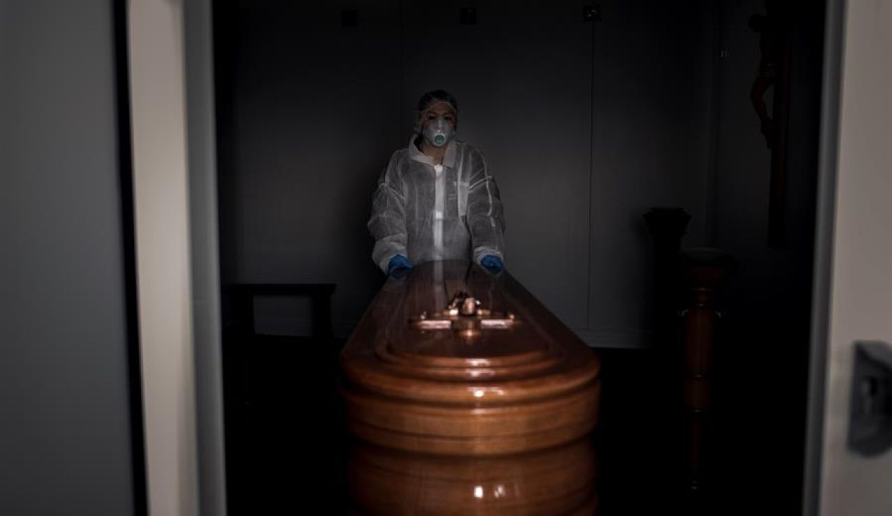 Una operaria transporta un ataúd con un fallecido por coronavirus en Ourense