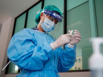 Una doctora con material de protección manipulando un medicamento