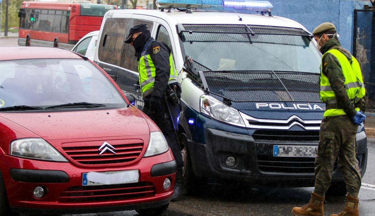 Un militar del Ejército y un agente de la Policía Nacional realizan controles de tráfico a la salida de la ciudad durante un viernes del estado de alarma
