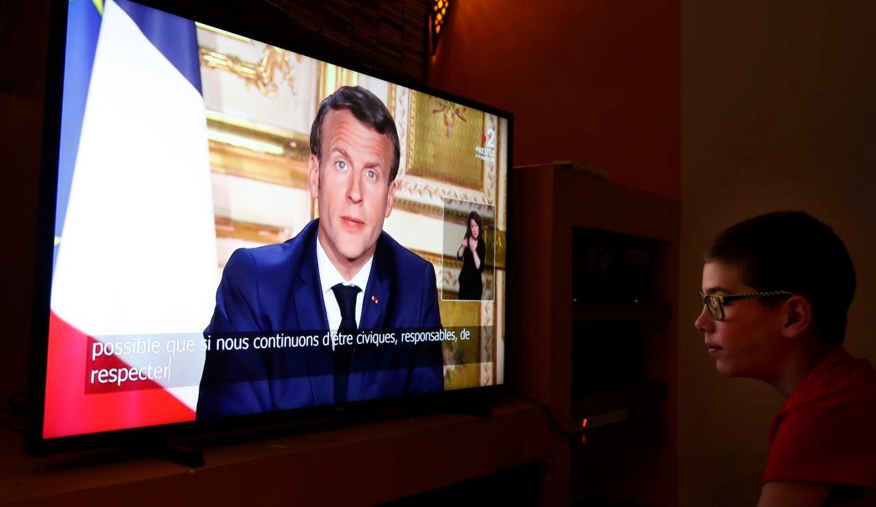 Un joven ve la comparecencia de Emmanuel Macron por televisión