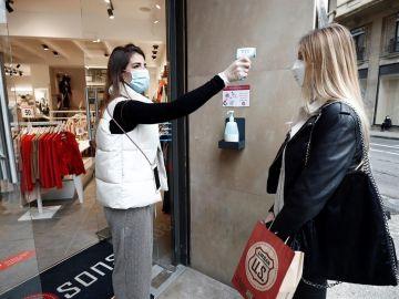 La encargada de una tienda de ropa toma la temperatura a una trabajadora