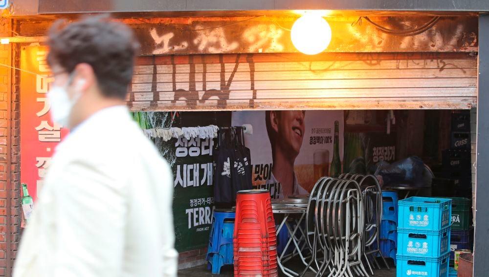 Un hombre pasa por delante de un bar en Sinchon, Seúl